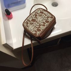 Make me an offer Small brown purse with lace. 1 main pocket. A place for your phone (largest phone it fits is an iPhone 6). And a pocket that can hold 6+ cards. Used only a handful of times. Claire's Bags Crossbody Bags