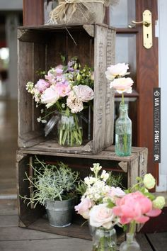 Pretty, rustic, romantic display: Flowers in mixed bottles and vases, with wooden crates.