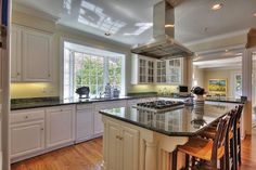 A center island with built-in cooktop and breakfast bar highlights the kitchen.
