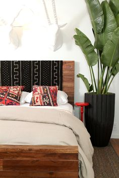 Throw a blanket or rug over a headboard to change up the look . Love this Potted plant...