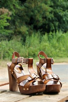 Our Queen City Heel - Brown is too adorable! It's a platform heel with a rustic wood finish. It has a 5'' heel with straps that run along the top of the front. Adjustable ankle buckle and buckle across the foot for accent.