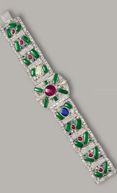 JADEITE, DIAMOND AND GEM-SET WATCH The flexible watch highlighted opening to the dial cover with two step-cut emeralds and an oval ruby weighing approximately 3.50 carats, open to reveal a circular dial