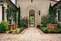 The entry to the courtyard shows how the front bubbling urn fountain features are centered with the walkway and front door, and how the dual fountains frame the walkway, all working together to provide a soothing, yet dramatic space.  Since the home's materials were neutral, adding a wide variety of planting colors soften the walls and ground plane and provide the contrast in color that was desperately needed.