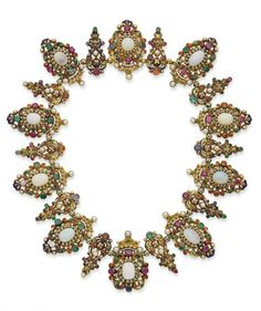 A 19TH CENTURY AUSTRO-HUNGARIAN NECKLACE AND TIARA HAIR-PIECE.The necklace consists of a series of ovals centered with a white opal in a circle of enameled scrollwork punctuated with emeralds, rubies, garnets, sapphires and pearls, surmounted by a small crown with enamel and set with emeralds, rubies, sapphires, garnets and pearls, 45 cm., front of a tiara similarly set