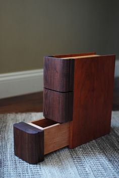 Brilliant design - looks like a book on the shelf, but has three small drawers for storage. Very nice...