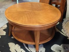 OAK FINISH ROUND COFFEE TABLE WITH SLIDING TOP REVEALING A STORAGE COMPARTMENT. NICE CLEAN CONDITION. 19H X 36W
