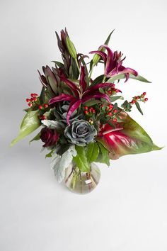 Sophisticated burgundy and green floral arrangement using a combination of kale, lily, rose, anthirium and greenery presented in a clear glass vase. From Urban Orchid via @BloompopHQ