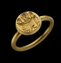 Gold ring, the hoop supporting the round bezel engraved with a marriage scene in which Christ unites the man and woman by joining their right hands together. 7th century.