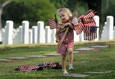 Madeline Grace Wallace, 4, carries flags at the National Cemetery in Little Rock, Ark., Friday, May 25, 2012. The girl and her mother visited the cemetery to place flags on graves for Memorial Day. Photo: Danny Johnston / AP