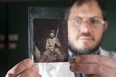 Processing archivist Andrew Baraniak holds a rose ambrotype from 1861 at the Wisconsin Veterans Museum in Madison. The image is on a type of glass negative that could be made to appear as a positive by backing it with black varnish or paper. Last fall the Wisconsin Veterans Museum was awarded a $31,000 grant to digitize the museum's collection of Civil War images.