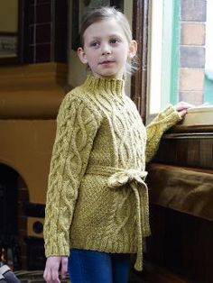 Charlotte - Knit this childrens cable tunic from Once Upon a Time. Designed by Marie Wallin using the wonderful tweedy yarn Felted Tweed Aran (wool), this sweater has an all over cable pattern, stand up collar and the addition of a belt.
