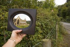 "Claude glass:  late 18th century mirror carried by tourists.  ""The device was typically pocket-size, with convex, gray-colored glass. When viewers looked into it, the convex shape pushed more scenery into a single focal point and the color of the glass changed the tones to be more pleasing to the eye by the standards of the contemporary picturesque paintings, which had a limited color palette. The constructed image was thought to be even more beautiful than reality."""