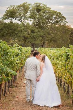 Bride + groom stealing kisses amidst the vineyard and oak trees