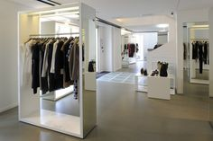 """This """"U"""" shaped shop has windows on three sides with an imposing Haussmanian architecture that divides the facade to repetitive and relatively small and deep windows. The space was cleaned up, and our aim was to focus on the clothes and the furniture."""