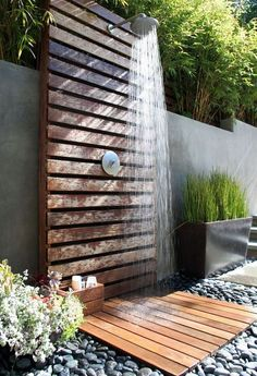 ▷ 1001 + Ideas and pictures about garden shower build yourself .- ▷ 1001 + Ideen und Bilder zum Thema Gartendusche selber bauen floor of many small black stones, wall of wood, garden shower, self-build ideas, gray flower pots with green plants -