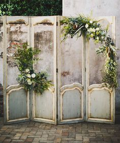 Vintage door screens decorated with greenery and flowers. Love this as a ceremony backdrop.