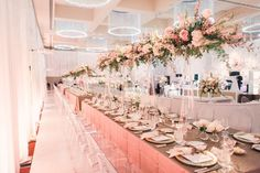 Long reception table with tall centerpiece design pink flowers, leaves, white…