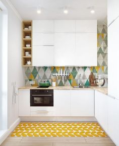 Small white kitchen with wood countertop and colorful accents.