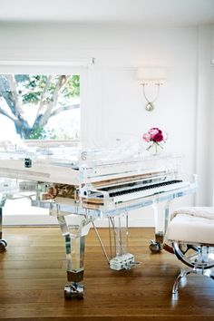 At home with Miranda Kerr: The custom-made baby grand piano in the living room, by the Crystal Music Company in the Netherlands, is an homage to her beloved grandmother, Ann, who taught a young Miranda to play. The vase atop the piano is the 20cm 'Rose Bowl' from the Miranda Kerr for Royal Albert collection; the wall sconce is from Circa Lighting.