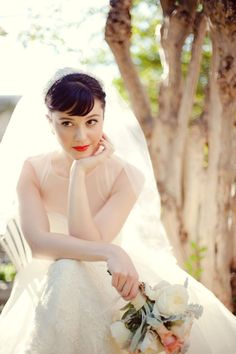 Bride sitting pose with hand under chin and elbow on knee, other hand holding bouquet
