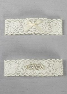 """This delicate lace garter set is embellished with an intricately beaded applique on the keepsake garter and a small satin bow on the toss garter. With elegant decoration and a sophisticated style, this garter set will be the perfect compliment to your beautiful gown. Features and Facts:   15"""" around unstretched, 1.75"""" W"""