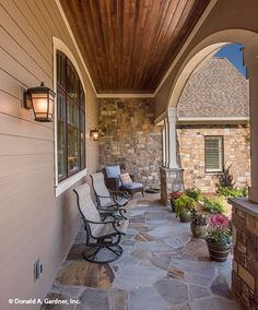 This front porch features so many unique elements. From the wood panel ceiling to the stone accents and arched entry. Dream house plan, The Chesnee #1290.