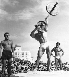 """ George Eiferman entertaining a huge Muscle Beach crowd while playing ""Ain't She Sweet"" on his trumpet while pressing a 135 pound olympic barbell for reps. """