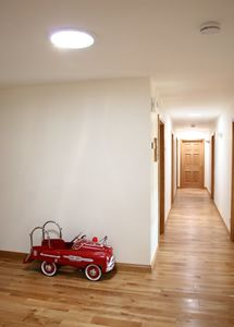 Two Solatube 160 DS Daylighting Systems bring bright, natural light to this windowless hallway. - Solatube UK