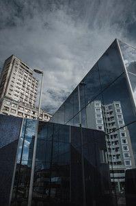 No centro de São Paulo, um prédio ocupado por sem-tetos (ao fundo) próximo ao metrô, cujos vidros refletem um edifício recém-reformado: a cidade mudou menos do que se previa e de modo diferente