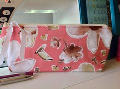 This coral/pink 100% cotton fabric, has beautiful dogwoods and magnolias flowers. This case is very soft - as it had double batting and no interfacing. Fully lined in Kona Snow fabric.  The shape of the case is sleek with curved corners at the top towards the zipper for a secure side-to-side closing. The bottom of the case has a flat bottom that allows it to stand on its on.  It measures aprox 9.00 inches wide (23.5 cm) and 4.0 inches tall (10.2 cm), and 1.5 inches across the bottom (3.8…