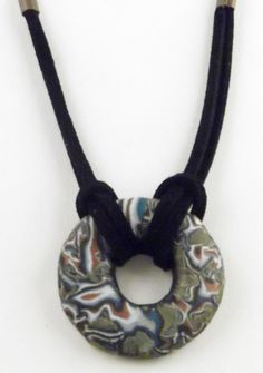 Polymer clay donut pendant strung with suede lace.