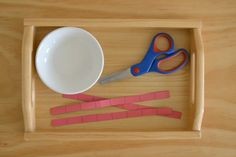 Toddler Practical Life: Scissor and cutting tray (18 months). Heavy weight paper helps keep the strip steady in the hand. The lines help with accuracy, but aren't necessary in the beginning. A small bowl for scraps ensures quick and easy clean up.