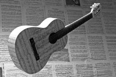 Old guitar decorated with sheet music. Doug St Allan
