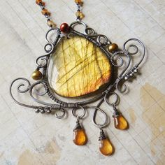 $122.00 Inside elegant swirls of antique sterling silver sits the spirit of the greenwood-- a golden green labradorite, shining bright like the sun setting through the forest canopy. It is adorned with freshwater pearls in bronze and gilded green, as well as several amber hessonite garnet droplets.