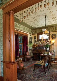 Glimpsed from the entry through the restored colonnade framed by a beaded valance, this end of the parlor leads to the dining room beyond velvet portieres.