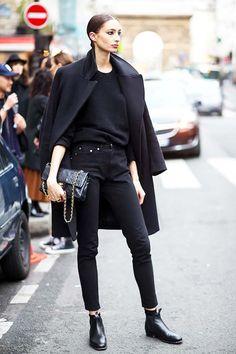 look all black com botas e sobretudo