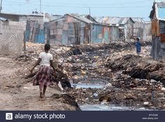 http://www.alamy.com/stock-photo-haiti-girl-walking-by-open-sewage-in-the-slums-of-of-cite-soleil-port-32235837.html