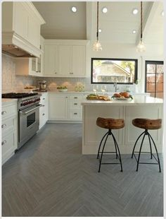 "Grey tile ""hardwood"" floors layed out in a herringbone pattern. I ♡ everything about this kitchen - the floors, lighting, window above the sink, counter stools, wolf range, white granite counter tops, cabinets, cabinetry hardware, you name it!!"