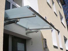 Edelstahlvordach Miami ein beleuchtetes Echtglas Haustürvordach mit Edelstahlhalterungen und Halogen Energiespar Lampen.