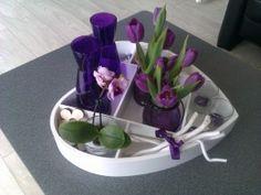 Een letterbak liggend in de plaats van hangend, gevuld met vaasjes met bloemen, kaarsjes, takjes, schelpen enz