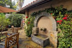 Talavera tile decorates a wall fountain with a Colonial stone surround in the courtyard.