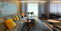 As poltronas pretas harmonizam com todo projeto decorativo. O sofá preenche a parede e comporta os diversos convidados que o proprietário adora receber, além de contar com puff que segue a mesma tonalidade e função.