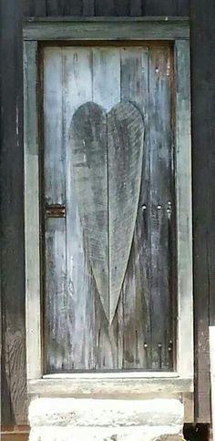 Gray wood door with large long heart, almost size of door