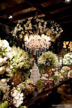 Mesa de doces clássica, móvel de madeira, com arranjos brancos, prataria e cristal. Elegante e chique. Foto: Rejane Wolff