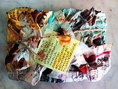 """""""Tuhoa tämä kirja"""" lahjapaketoituna kirjan sisällön hengessä. Paketointitarpeina mm. rypisteltyä sanomalehteä, pihalla talvehtinut narunpätkä ja pintaefekteinä kahvia, ketsuppia, sinappia, soijakastiketta ja punkkua."""
