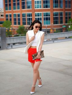 Crop top, orange skort, long vest, leopard clutch, ankle strap heels