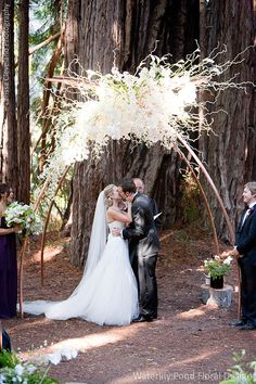 This white orchid wedding arch looks utterly magical in this ceremony among the redwoods. Wedding Event Design and Flowers: Waterlily Pond Floral and Event Design   Wedding Ceremony and Reception Venue: Santa Lucia Preserve    Wedding Planner: Allison Weddings  Wedding Photographer: Larissa Cleveland Photography