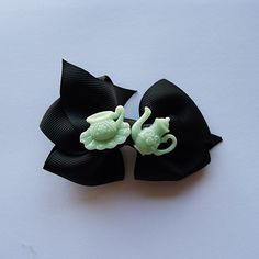Fancy a cup of tea? The perfect hair clip to wear for any high tea occasion!  Mint green acrylic teapot and cup charm centred in a black bow...