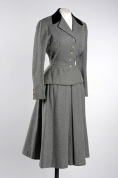 "1947-49 couture suit designed by Hattie Carnegie and owned by heiress Anne Moen Bullitt. ""The jacket has a fitted waist with padding on the hips, to make it flare out over the full skirt, giving the suit a typical 'New Look' style."" Leeds Museum."
