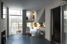 Stairs off the living room offer a view of the kitchen through a tall glass window and lead up to the mezzanine.